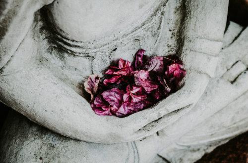 Buddha sitzend mit Blumen im Schoß