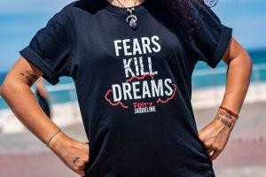 "Frau im schwarzen T-Shirt mit Aufschrift ""Fears Kill Dreams"""